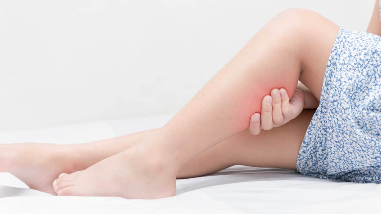 Leg pain or calf muscle in a girl on bed, healthy concept